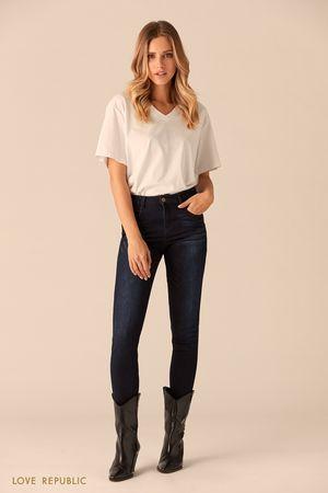 Тёмно-синие джинсовые брюки с потёртостями фото