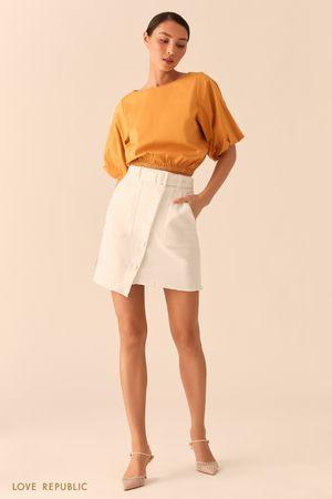 Джинсовая белая юбка асимметричного кроя с накладными карманами фото