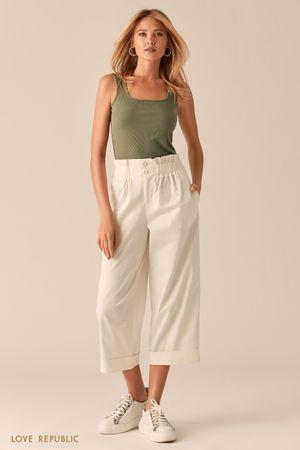 Укороченные широкие брюки с подворотами белого цвета фото